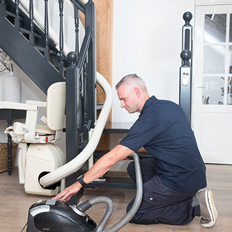 Stairlift technician cleaning up after an installation