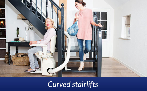 Stairlift with woman seated on curved staircase
