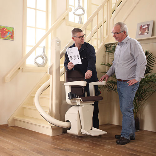 Stairlift advisor giving instructions about use of lift
