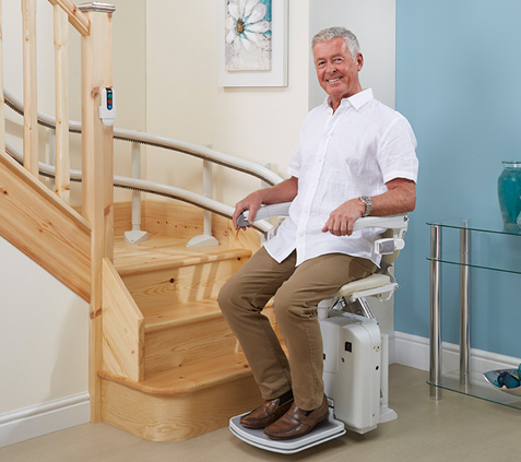 Stairlift on curved stair with seated man